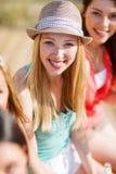 Menina com bebida e amigos na praia Imagem de Stock