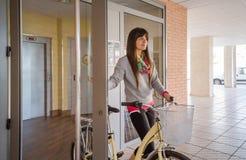 Menina com a bicicleta do fixie que abre uma porta de vidro para retirar fotografia de stock