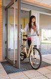 Menina com a bicicleta do fixie que abre uma porta de vidro para retirar imagens de stock royalty free