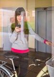 Menina com a bicicleta do fixie que sae do salão atrás de um vidro fotografia de stock royalty free