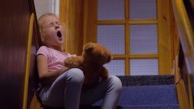Menina com bocejos do urso de peluche vídeos de arquivo