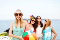 Menina com bola e amigos na praia Imagem de Stock