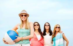 Menina com bola e amigos na praia Imagem de Stock Royalty Free
