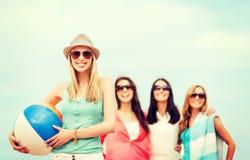 Menina com bola e amigos na praia Fotografia de Stock Royalty Free