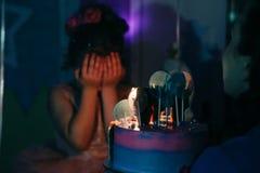 A menina com bolo de aniversário fechou seus olhos com suas mãos que fazem um desejo na sala escura, queimada velas imagens de stock royalty free