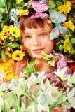 Menina com borboleta e flor na grama verde. Fotos de Stock