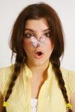 Menina com a borboleta no nariz Fotografia de Stock