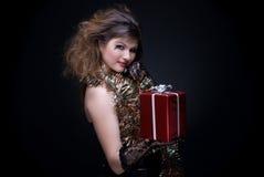 Menina com bordos, ouropel e presente vermelhos no bl Fotografia de Stock