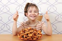 Menina com bruschette e polegares acima Foto de Stock