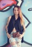 Menina com a câmera do vintage contra a parede dos grafittis imagens de stock royalty free