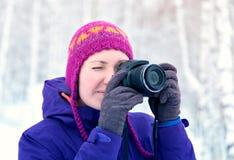 Menina com a câmera na floresta do inverno fotografada Fotografia de Stock