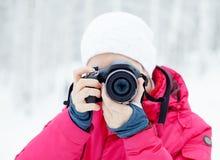 A menina com a câmera no fundo da neve do inverno Imagens de Stock Royalty Free