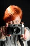 Menina com a câmera velha no fundo preto Imagens de Stock Royalty Free