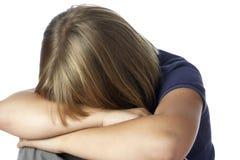 Menina com a cabeça enterrada nos braços Fotos de Stock