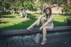 Menina com cabelo de fluxo no short curto e sapatas com os saltos que sentam-se em um banco imagens de stock royalty free