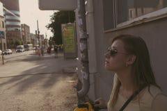 A menina com cabelo de fluxo nos óculos de sol está contra uma parede na cidade imagens de stock