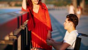 Menina com cabelo e Guy On vermelhos uma cadeira de rodas que fala na margem em uma noite do verão filme