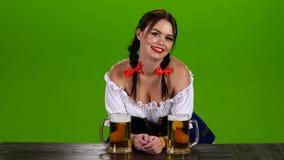 A menina com cabelo escuro e flertar em Oktoberfest oferece a cerveja Tela verde filme