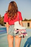 A menina com cabelo escuro longo é para trás com os patins de rolo em seu ombro Noite morna do verão no parque do patim imagem de stock