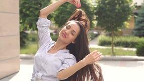 Menina com cabelo longo luxuoso em um parque da cidade filme