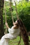 A menina com cabelo longo no vestido branco está montando o balanço da corda nas frentes Imagem de Stock