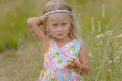 Menina com cabelo longo que anda ao longo do campo em um dia de verão morno Foto de Stock Royalty Free
