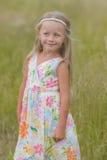 Menina com cabelo longo que anda ao longo do campo em um dia de verão morno Fotografia de Stock