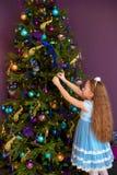 Menina com cabelo longo que decora a árvore de Natal imagens de stock