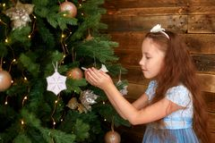 Menina com cabelo longo que decora a árvore de Natal foto de stock royalty free