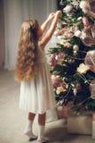 Menina com cabelo longo que decora a árvore de Natal, vintage tonificado imagens de stock