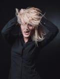 A menina com cabelo louro no fundo preto Imagem de Stock