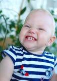 Menina com cabelo louro que sorri e que faz caretas Imagens de Stock