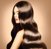 Menina com cabelo ondulado saudável longo. Fotografia de Stock