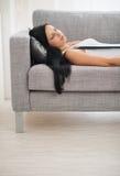Menina que dorme no sofá na sala de visitas Fotografia de Stock Royalty Free