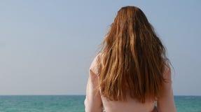 Menina com cabelo vermelho do gengibre longo que aprecia o seascape Brisa de mar que joga com cabelo fotografia de stock