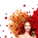Menina com cabelo vermelho encaracolado e as rosas vermelhas bonitas Fotografia de Stock Royalty Free
