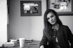 Menina com café A menina bonita nova está sentando-se em um café e Imagem de Stock Royalty Free