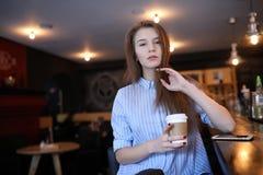 Menina com café A menina bonita nova está sentando-se em um café e Fotografia de Stock Royalty Free