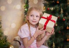 Menina com caixa atual que quer saber no Natal Imagens de Stock