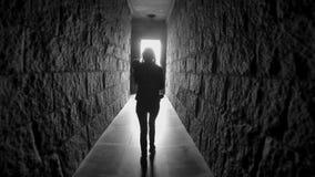 Menina com caminhadas longas do cabelo abaixo de um túnel escuro do corredor com sua parte traseira