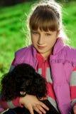 Menina com a caniche preta na natureza Imagens de Stock Royalty Free