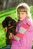 Menina com a caniche preta na natureza Fotografia de Stock Royalty Free