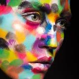 Menina com a cara colorida pintada Imagem da beleza da arte Fotos de Stock Royalty Free