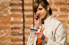 Menina com cartão de crédito e o telefone móvel Fotografia de Stock