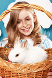 Menina com a cesta com ovos da cor e o coelhinho da Páscoa branco Foto de Stock Royalty Free