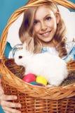 Menina com a cesta com ovos da cor e o coelhinho da Páscoa branco Foto de Stock