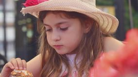 Menina com chapéu de palha que come seu sanduíche e que joga com balão filme