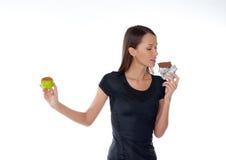 Menina com chocolate e maçã nas mãos Imagens de Stock