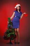 Menina com coração do brinquedo perto da árvore de Natal Imagem de Stock Royalty Free