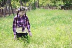 Menina com a coroa da flor no jardim Imagens de Stock Royalty Free